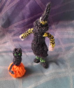 Tiny knitted witch and her cat and her pumpkin.